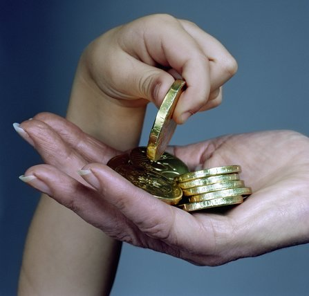 Girl (3-5) placing chocolate coins in to woman's hand, close-up